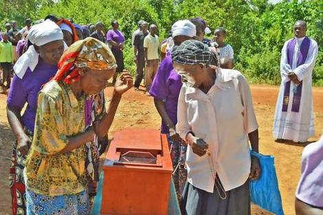 Faithful of the St Leo the Great Mban Catholic Church line up to view a coffin-like box modified with a mirror in Siaya County on February 19, 2020.