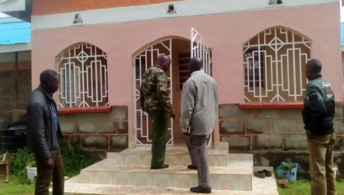 Kenya Police officers pictured outside a house designated as a crime scene.
