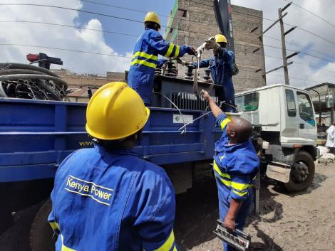 Kenya Power and Lighting Company engineers load a transformer into a lorry.