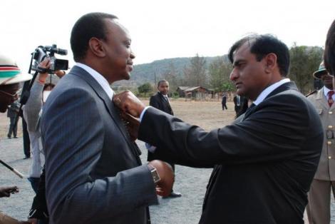 Devki Group of Companies founder Narendra Raval (right) fixes President Uhuru Kenyatta's tie
