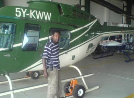 Photo of Evans standing next to KWS helicopter.