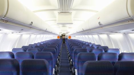 A handrail is located below the overhead bin and is essential for passengers to use when moving around the cabin