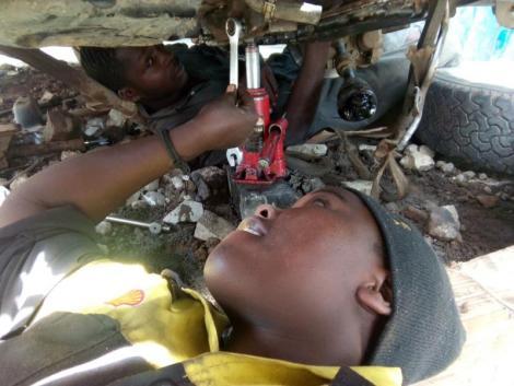A female mechanic working on a car in a Nairobi garage