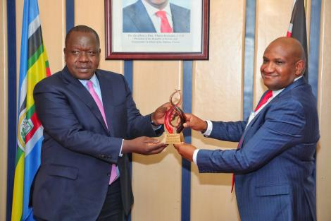 Cabinet Secretary Dr Fred Matiang'i receiving an award from KRA boss James Mburu on Wednesday, July 14, 2021