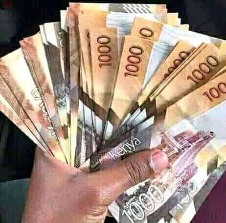 A Picture of a hand holding Kenyan notes.