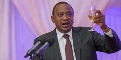 President Uhuru Kenyatta holds a glass of champagne during a past event