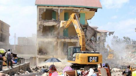 A bulldozer pulling down a house