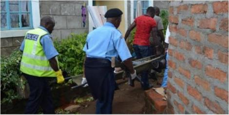 A file image of officers ferrying a body from a residential area.