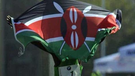 An athlete celebrates with a Kenyan flag after winning a race