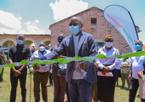 Safaricom PLC CEO Peter Ndegwa cuts a ribbon to mark the official opening of a fully furnished computer laboratory in Borstal Prison, Juvenile section in Kakamega county.