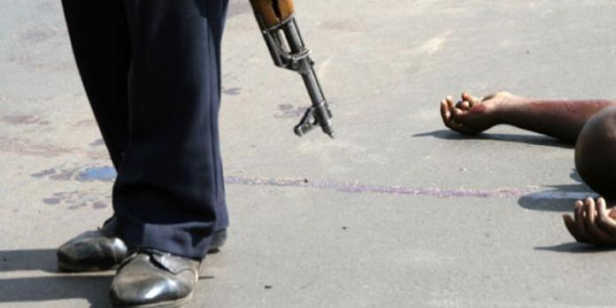 A police officer walks past one of bodies of the suspects at the scene of the shooting on Langata road, Nairobi on January 19, 2011