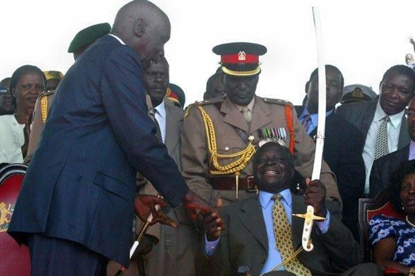 Outgoing president Daniel Moi hands over the instruments of power to incoming Mwai Kibaki at Uhuru Park on December 30, 2002.