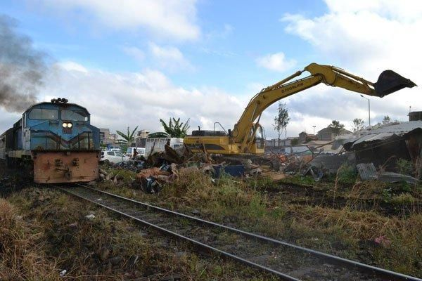 Image of a bulldozer demolition structures next to a railway line