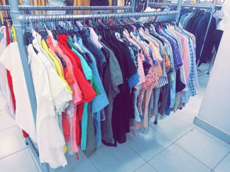 Retail store in a Kenya selling second hand T-shirts in different colors such as red and yellow.