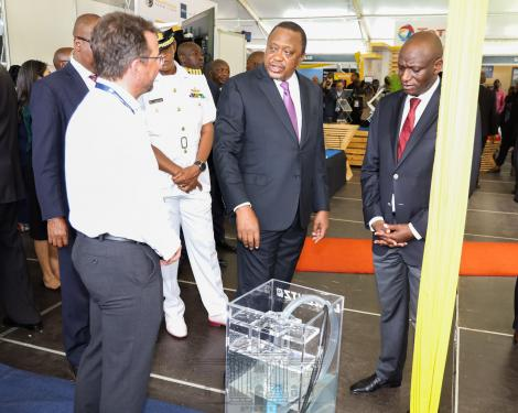 President Uhuru Kenyatta is taken through a demonstration at a stand during the 6th Global Off-Grid Solar Forum and Expo in Nairobi on Tuesday, February 18.