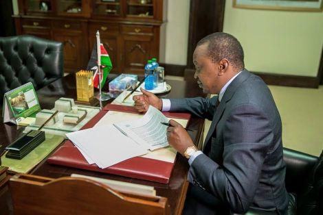 President Uhuru Kenyatta reading documents in his office