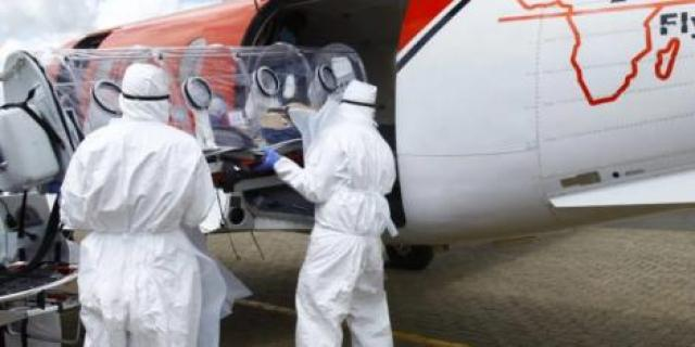 AMREF Flying Doctors personel load a portable isolation chamber onto a plane.