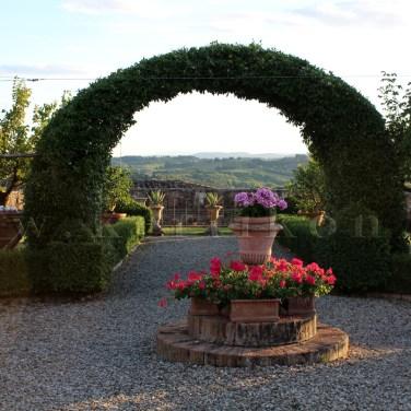 Villa di Geggiano, a virágoskert hátterében Siena tájának látványa