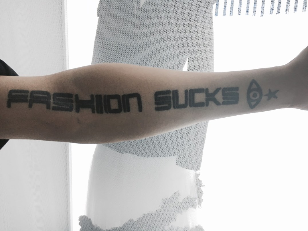 """Fashion Sucks"" tattoo on designer Justin Chou (by Darice Chang)"