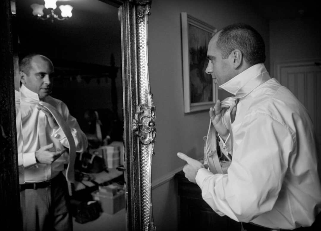 Groom looking in mirror putting on tie at Lemore Manor