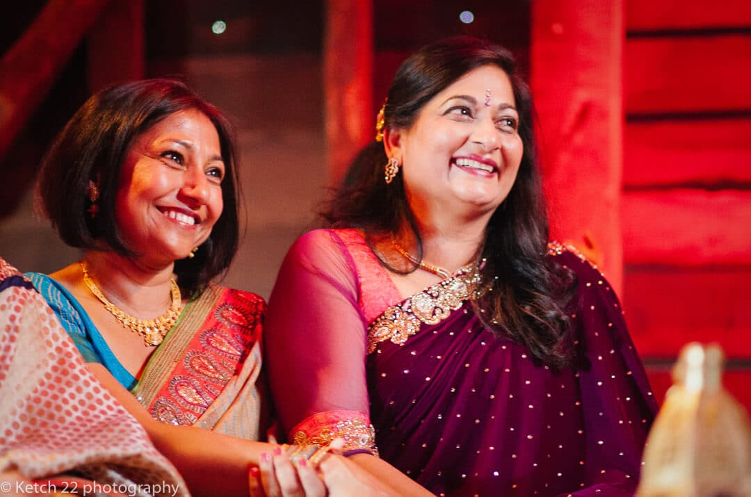Mums wearing colourful Indian costume laughing at Hindu wedding