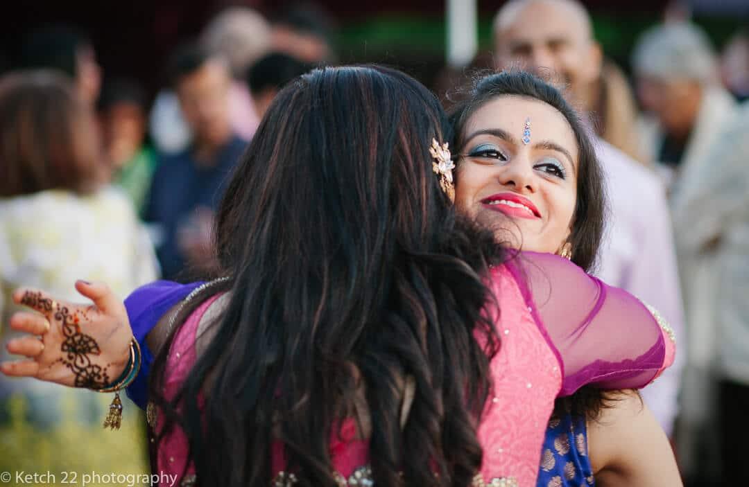 Wedding guests embracing at Hindu celebration