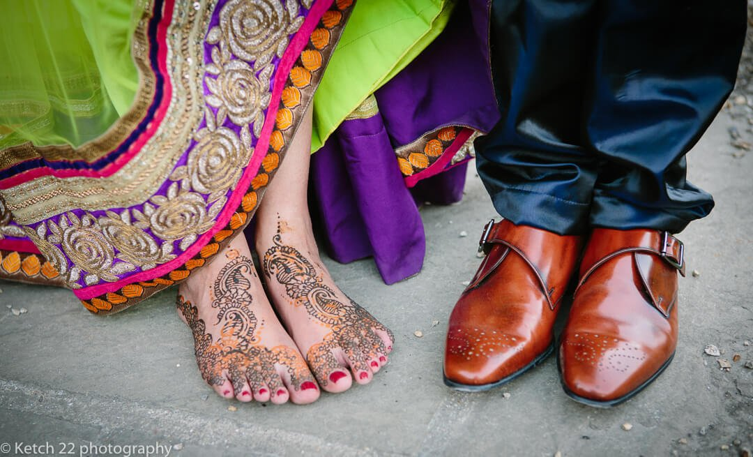 Bride painted feet and grooms red leather shoes at hindu wedding