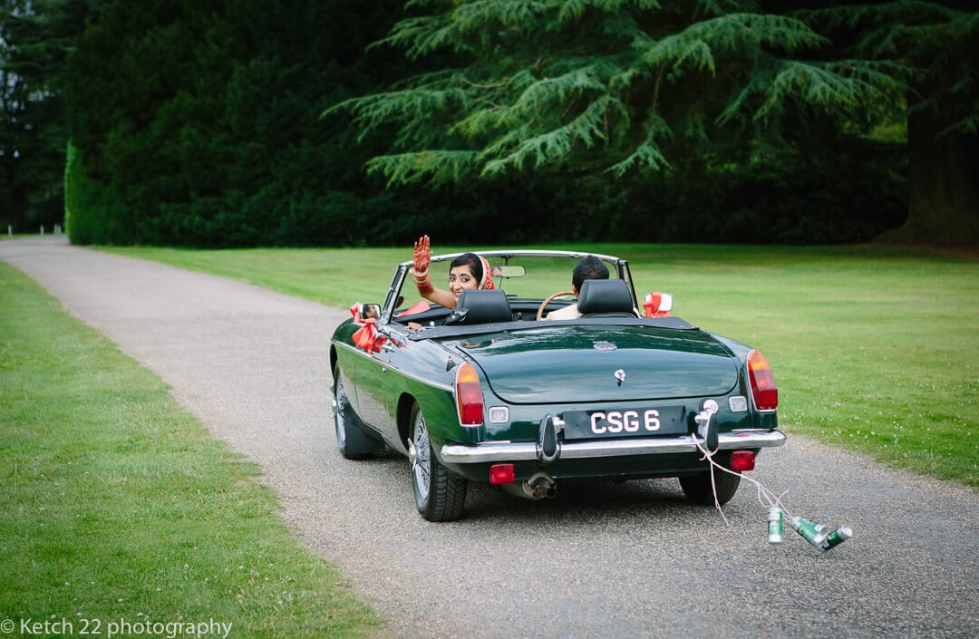 Hindu bride waving from green wedding car with cans trailing