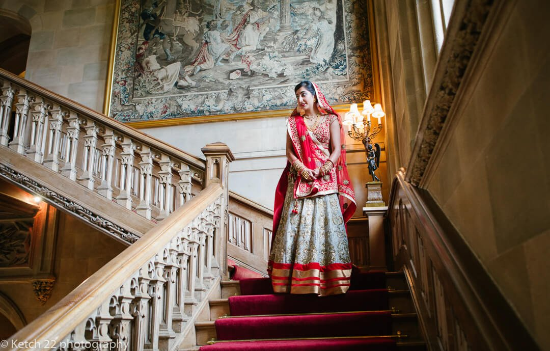 Indian bride in red and gold ascending staircase
