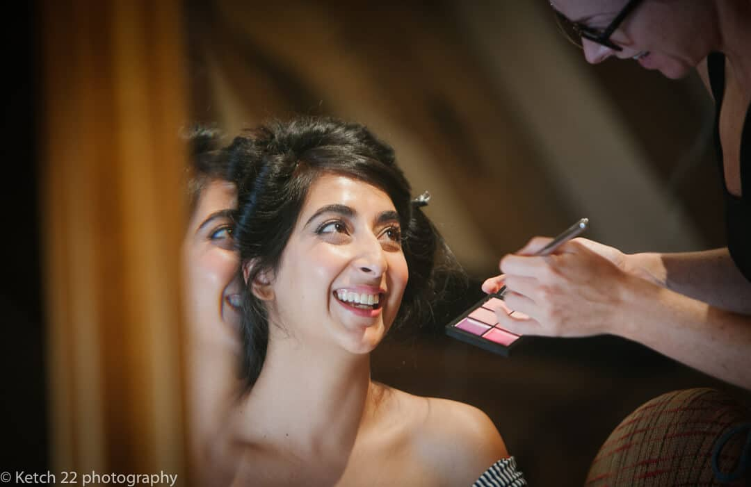 Indian bride in mirror getting ready for Hindu wedding reception at Micklefield Hall