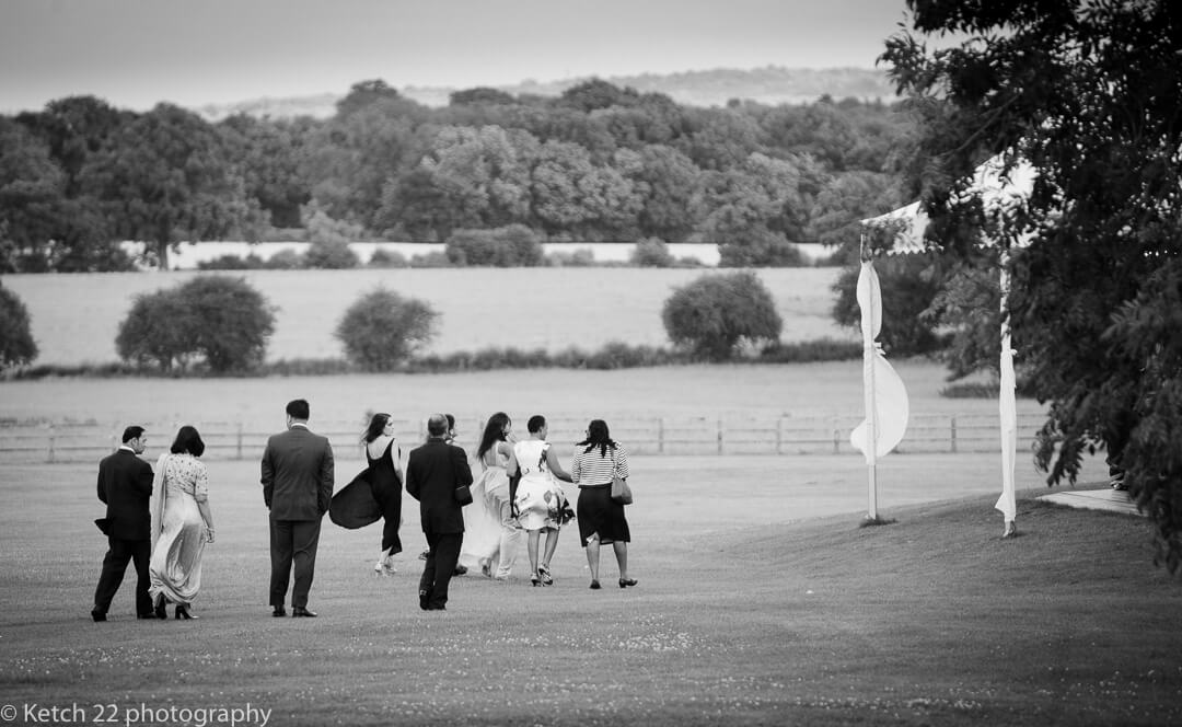 Wedding guests walking to marquee at summer reception