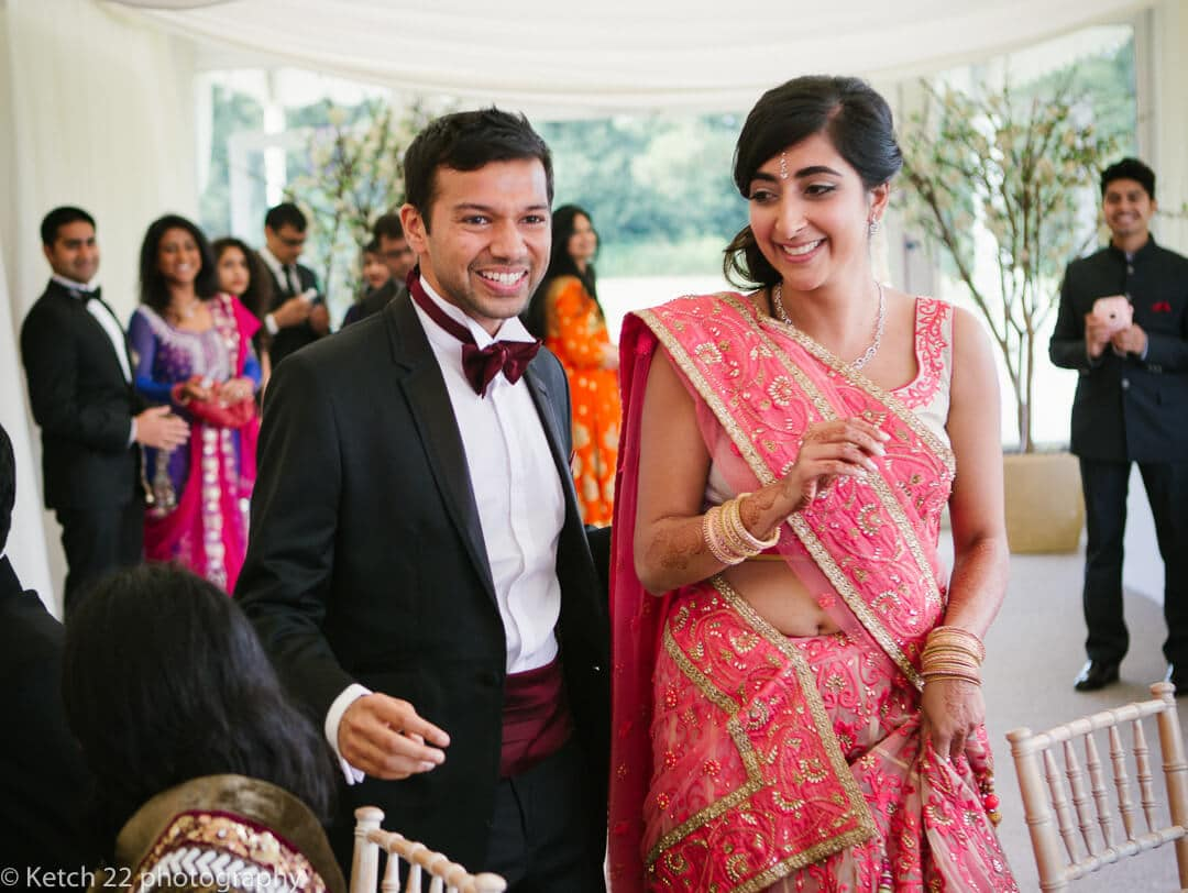 groom in tuxedo and bride in pink dress at Indian wedding