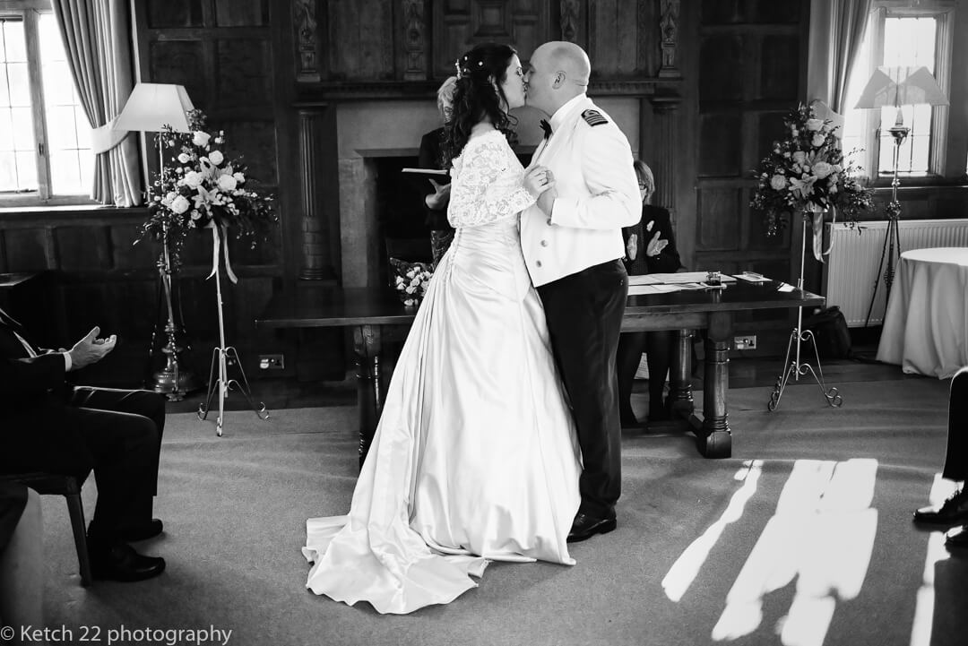 Candid wedding photo of bride and groom kissing at wedding ceremony
