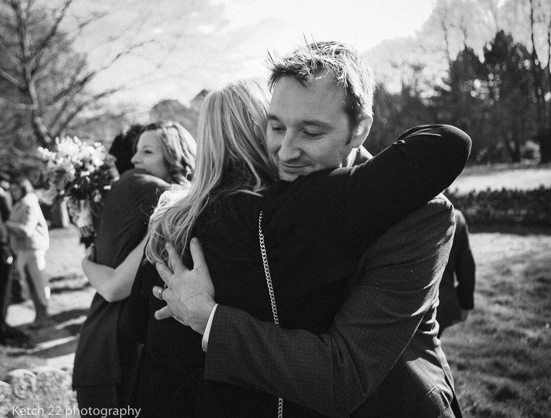 Groom hugging wedding guest at spring wedding