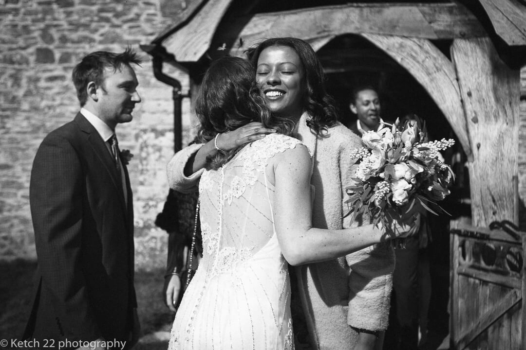 Bride hugging wedding guest outside church in Herefordshire