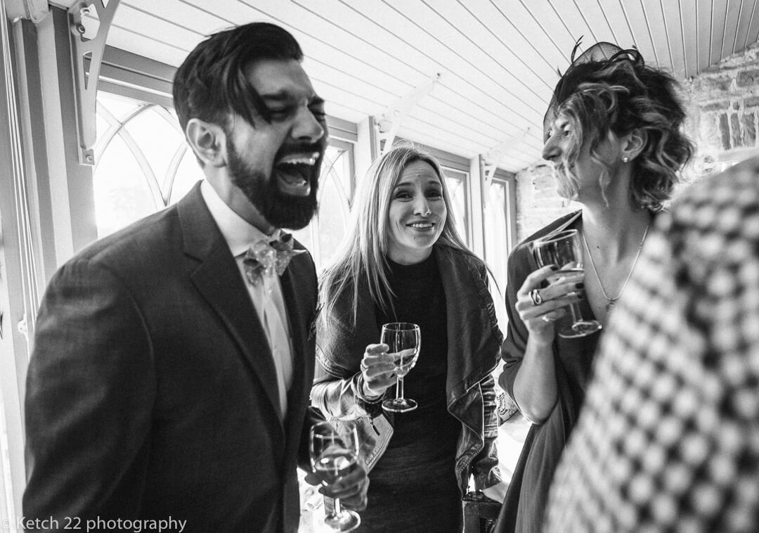 Documentary wedding photo of guests drinking and laughing