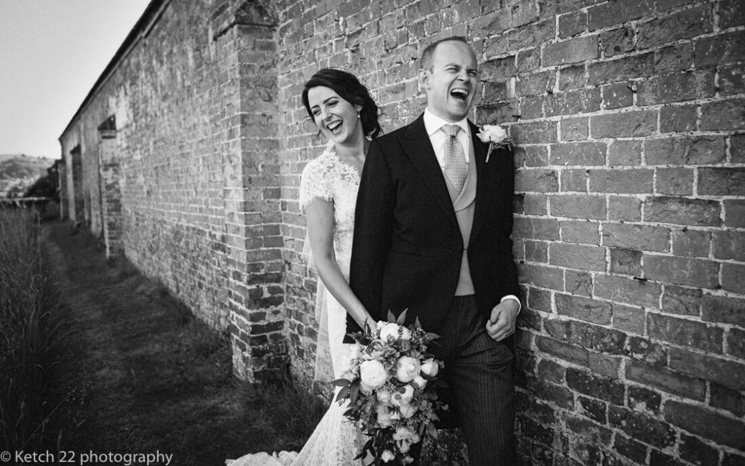 Bride and groom laughing in walled garden