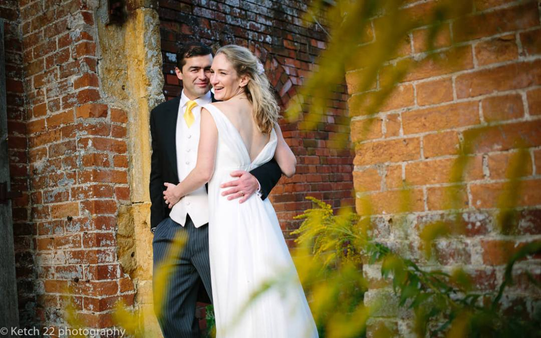 Portrait of bride and groom in walled garden