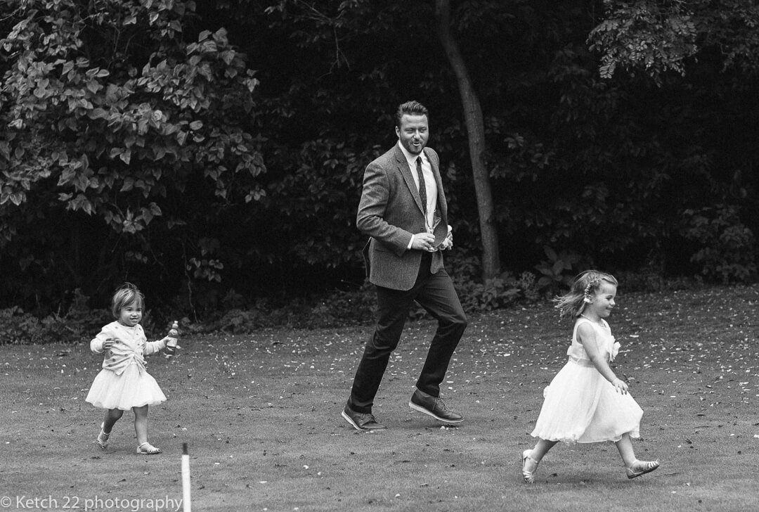 Father running wth his kids at Gloucestershire wedding