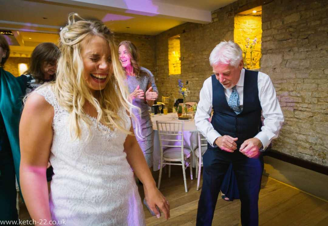 Bride laughing on dance floor at Gloucestershire wedding