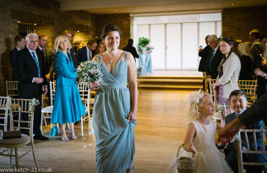 head bridesmaid enters wedding ceremony