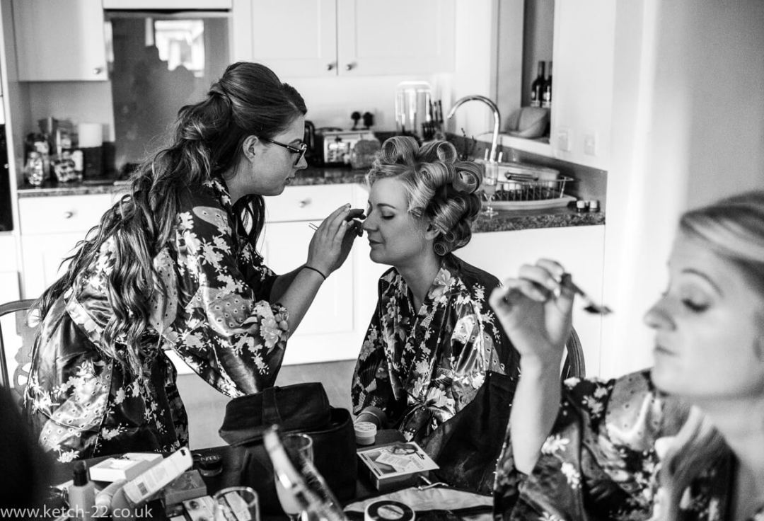 Black and white photo of bridesmaid having makeup applied