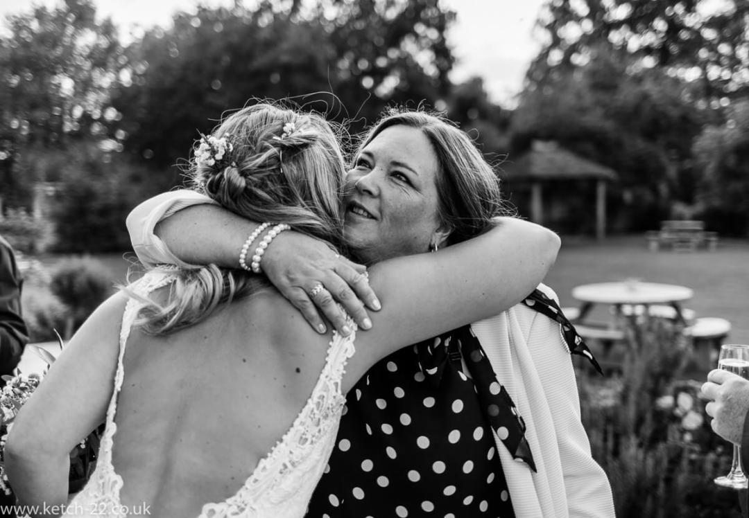 Bride hugging friend after wedding ceremony
