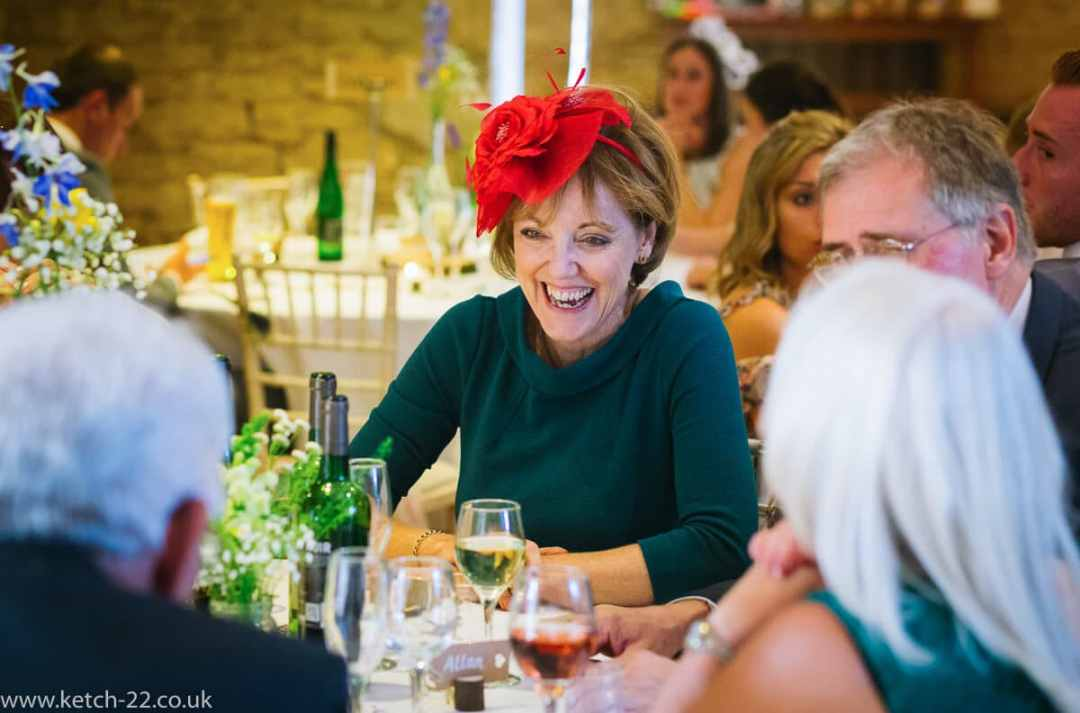 Lady with red hat laughing at wedding breakfast