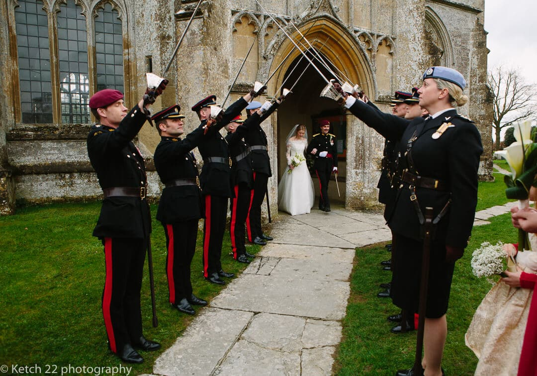 Bride and groom saluted with swords at army wedding