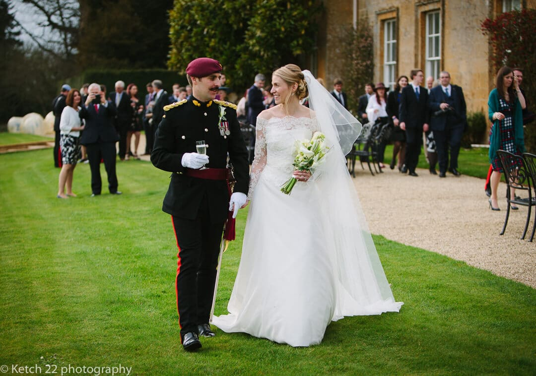Bride and groom in army uniform walking in front of North Cadbury Court