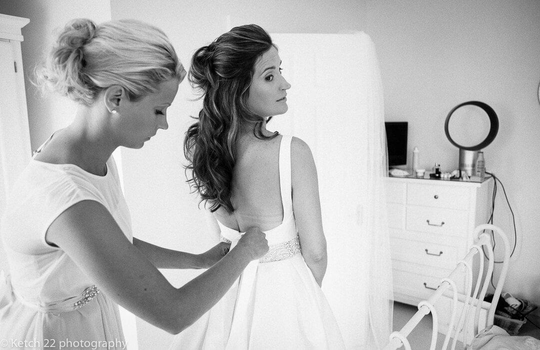 Bride having back of dress done up at wedding preparations