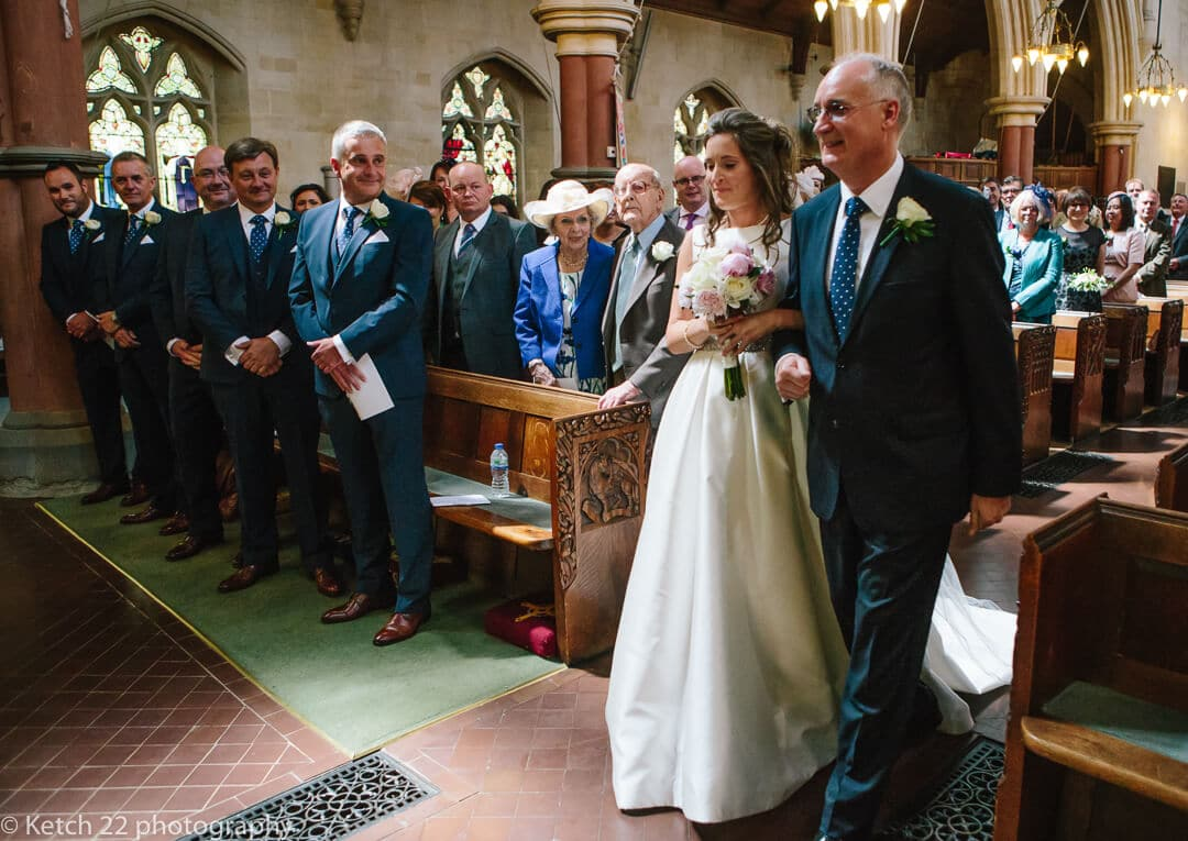 Father and bride walking down church aisle