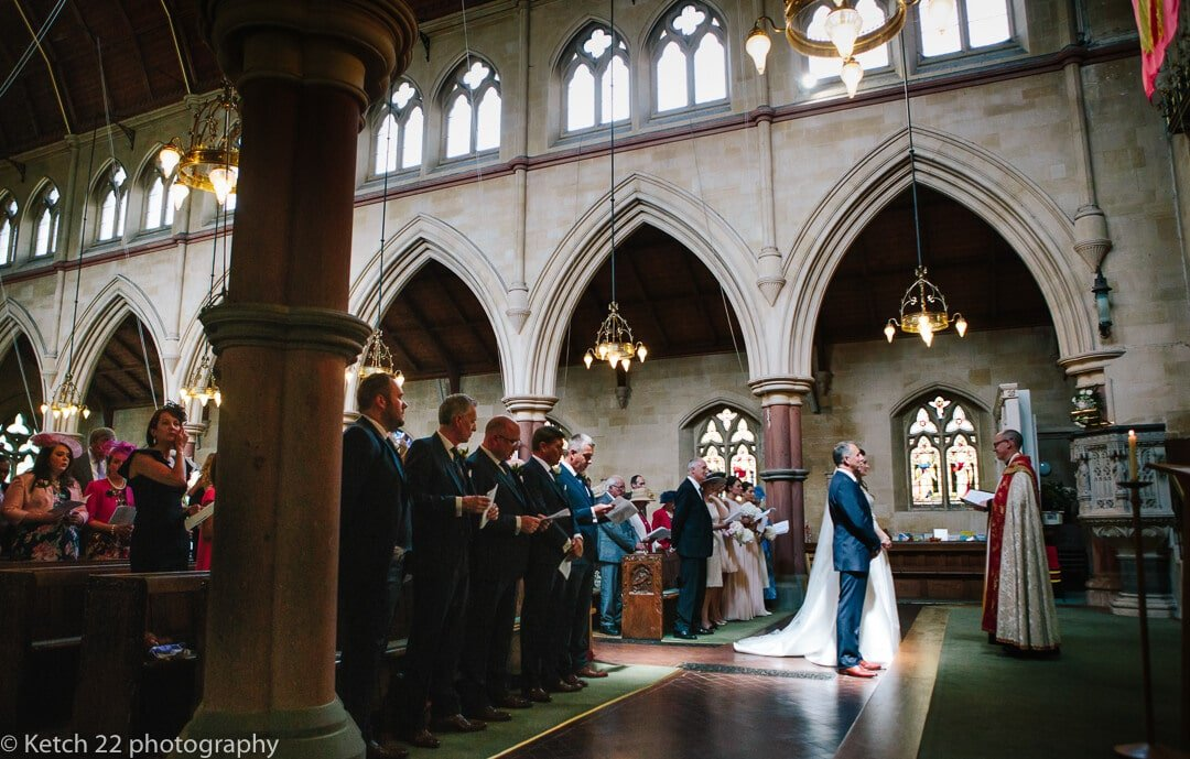 side view of bride and groom and wedding guests at church in Gloucestershire
