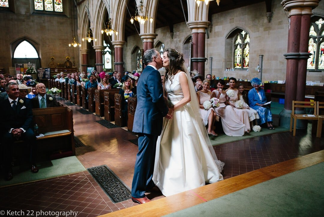Bride and groom kissing with guests clapping at wedding ceremony